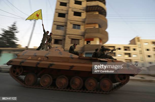 Fighters from the Syrian Kurdish People's Protection Units drive a tank in the street in Qamishli waving a YPG flag as they celebrate after the...
