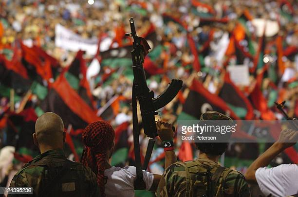 A fighters holds up an assault rifle as thousands of Libyans rally for their revolution in Green Square now renamed Martyrs Square by revolutionary...