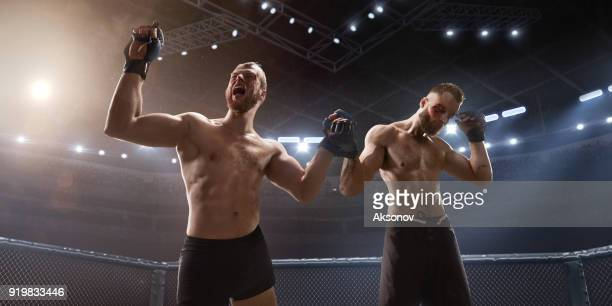 MMA fighters in professional boxing ring emotionally rejoices in victory
