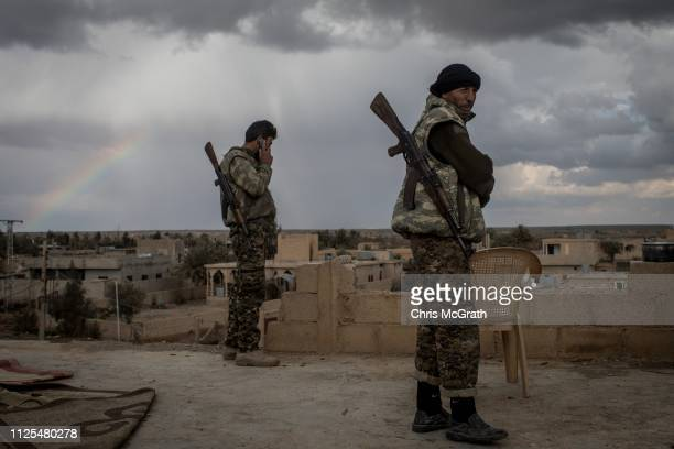 Fighters keep watch from a rooftop on the outskirts of Bagouz on February 17, 2019 in Bagouz, Syria. Fighting continues in a small section in the...