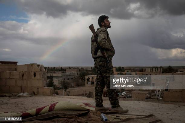 SDF fighters keep watch from a rooftop on the outskirts of Bagouz on February 17 2019 in Bagouz Syria Fighting continues in a small section in the...