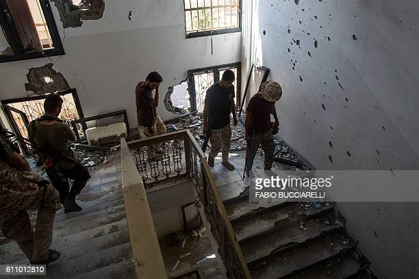 TOPSHOT Fighters loyal to Libya's Government of National Accord walk down the stairs of a liberated building on the frontline against Islamic State...