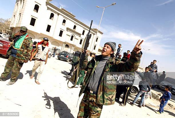 Fighters loyal to Libya's internationally recognised government celebrate as they come close to seizing the centre of Libya's eastern coastal city of...