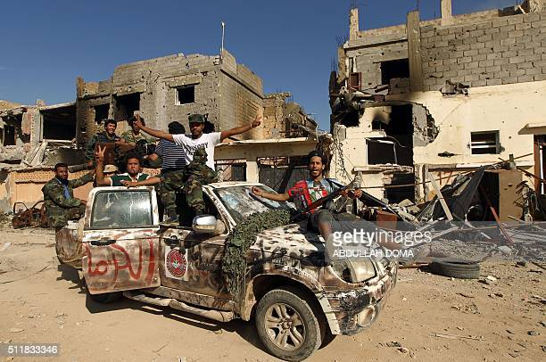 Fighters loyal to Libya's internationally recognised government celebrate in the street of Benghazi after taking control of the Islamist areas of the...