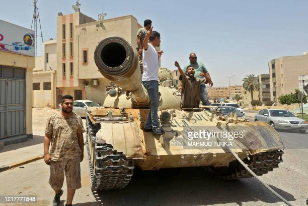 Fighters loyal to Libya's UN-recognised Government of National Accord stand atop a tank in the town of Tarhuna, about 65 kilometres southeast of the...