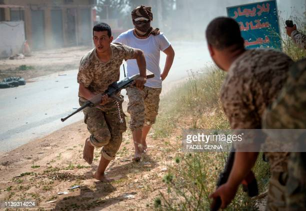 TOPSHOT Fighters loyal to the internationally recognised Government of National Accord run for cover during clashes with forces loyal to strongman...