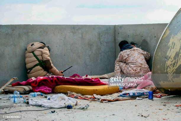 TOPSHOT Fighters loyal to the internationally recognised Libyan Government of National Accord keep a look out on the roof of a building in an area...