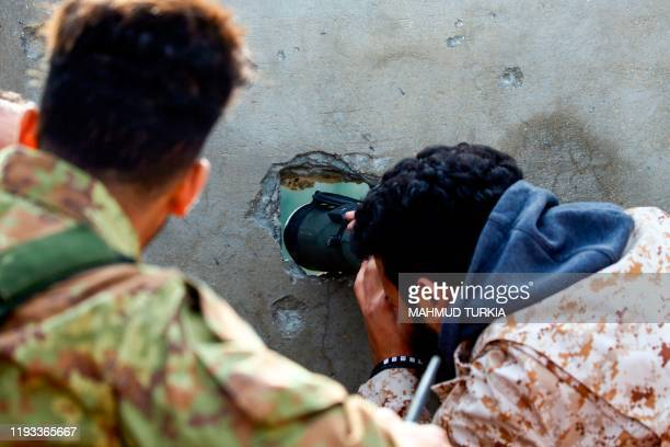 Fighters loyal to the internationally recognised Libyan Government of National Accord keep a look out on the roof of a building in an area south of...