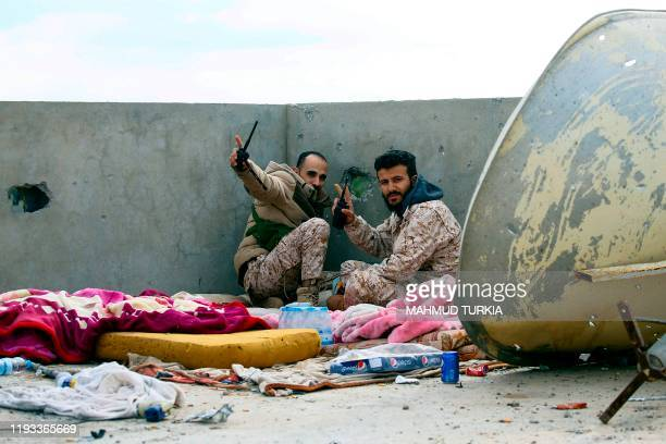 Fighters loyal to the internationally recognised Libyan Government of National Accord gesture as they keep a look out on the roof of a building in an...