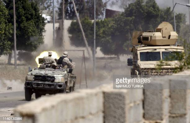 TOPSHOT Fighters loyal to the internationallyrecognised Government of National Accord fire a jeepmounted gun during clashes with forces loyal to...