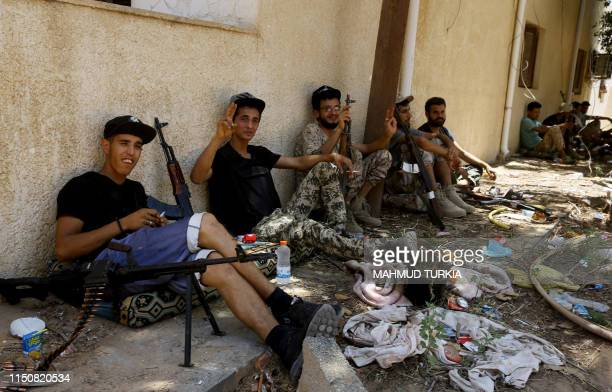 Fighters loyal to the internationallyrecognised Libyan Government of National Accord take a rest near their weapons in the alSawani area south of the...