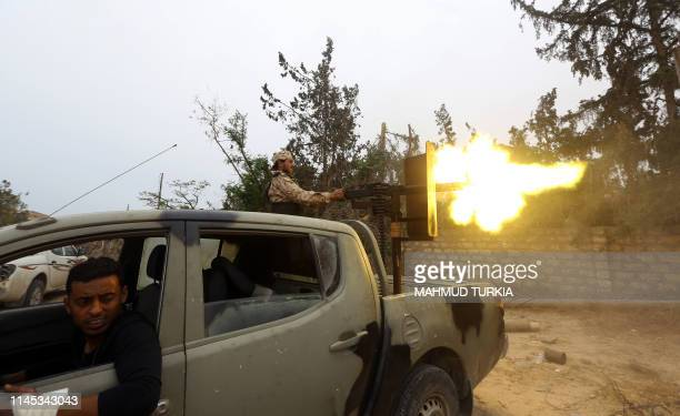 Fighters loyal to the Libyan internationallyrecognised Government of National Accord fire a heavy machine gun during clashes against forces loyal to...