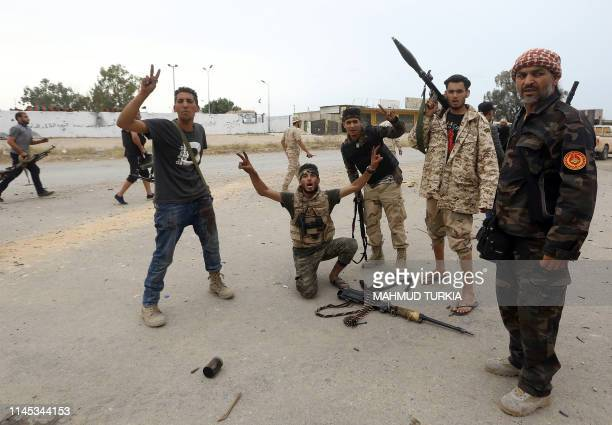 Fighters loyal to the Libyan internationally-recognised Government of National Accord gesture near the frontline during clashes against forces loyal...