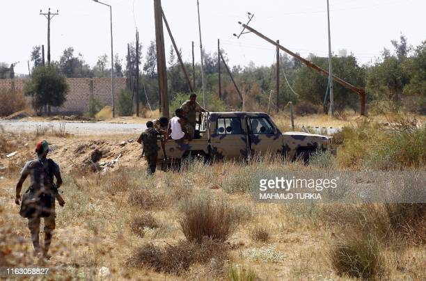 Fighters loyal to the UN-recognised Government of National Accord , get on board of a military vehicle during clashes with forces loyal to strongman...