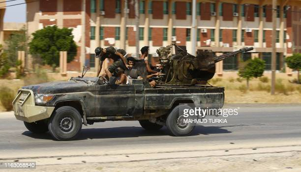 Fighters loyal to the UNrecognised Government of National Accord geare transported on board of a military vehicle during clashes with forces loyal to...