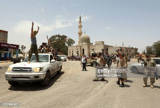Fighters loyal to the UN-recognised Libyan Government of National Accord celebrate together in the Qasr bin Ghashir district south of the Libyan...