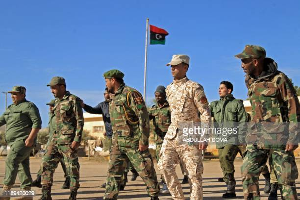 Fighters of a military battalion loyal to Libyan General Khalifa Haftar march during the morning assembly in the eastern city of Benghazi on December...