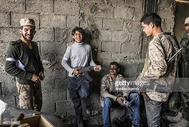 Fighters of Fajr Libya hide in defilated position while waiting snipers of Zintan forces to be wiped out during the clashes between rival Libyan Dawn...