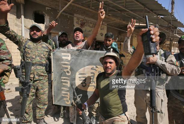 Fighters of Hashed Al-Shaabi flash the victory gesture as they hold upside down a banner bearing the logo of the Islamic State group, during the...