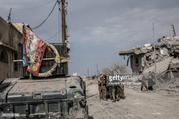 Fighters of the federal police, shiite religious flag hanging on their humvees, are seen in a district taken back from IS in western Mosul.
