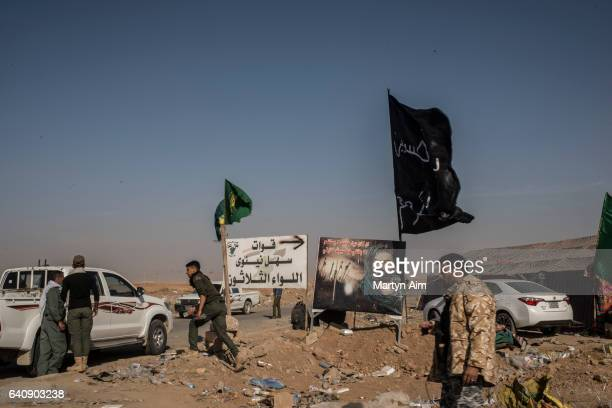 Fighters of the Hash'd al Shaabi or Popular Mobilisation Forces , Shia-dominated fighting units at a checkpoint flying flags of fighting units and...