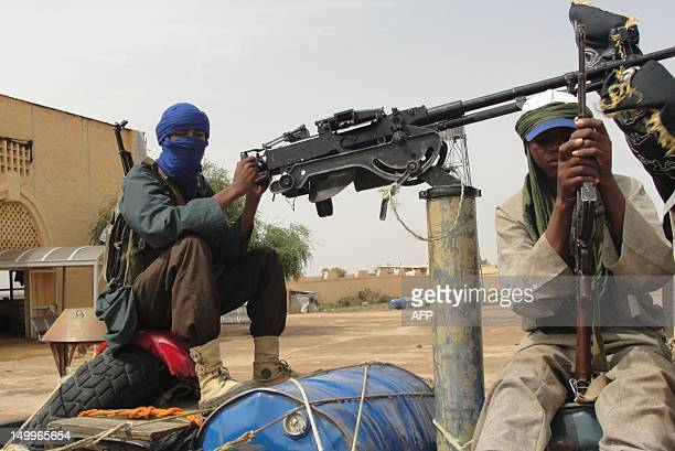 Fighters of the Islamic group of Mujao stand guard near the Gao airport as Burkina Faso's foreign Minister Djibrille Bassole meets with the Islamic...