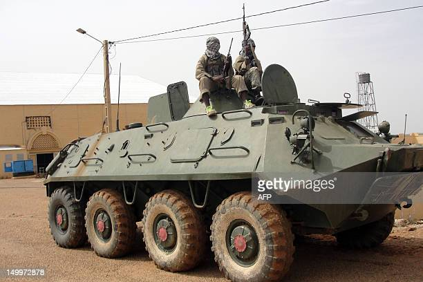 Fighters of the Islamic group the Movement for Oneness and Jihad in West Africa an AlQaeda offshoot stand guard on August 7 2012 on a tank abandoned...