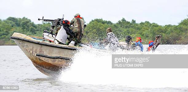 Fighters of the Movement for the Emancipation of the Niger Delta speed away from the militia's creek camp in the Niger Delta on September 17 2008...