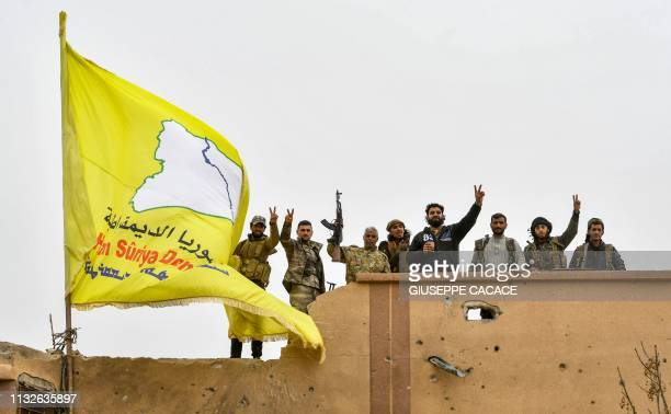 Fighters of the Syrian Democratic Forces flash the victory gesture next to their unfurled flag atop a roof at a position in the village of Baghouz in...