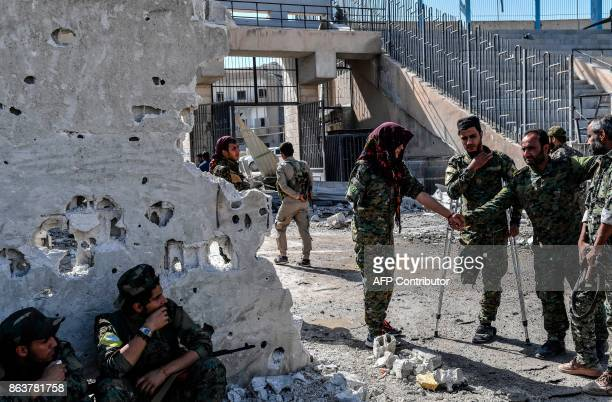 Fighters of the Syrian Democratic Forces gather at the stadium in Raqa to celebrate on October 20 after retaking the city from Islamic State group...
