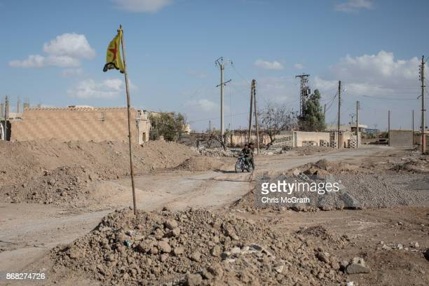 Fighters of the Syrian Democratic Forces ride a motorbike through a destroyed street in the western neighborhood of Jazrah on the outskirts of Raqqa...