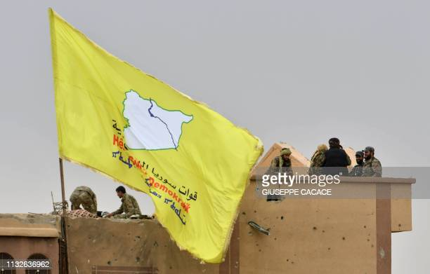 Fighters of the Syrian Democratic Forces stand atop a roof next to their unfurled flag at a position in the village of Baghouz in Syria's eastern...