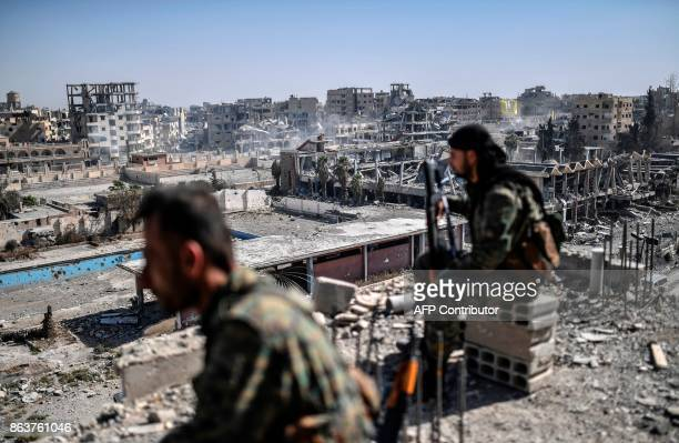 Fighters of the Syrian Democratic Forces stand guard on a rooftop in Raqa on October 20 after retaking the city from Islamic State group fighters SDF...