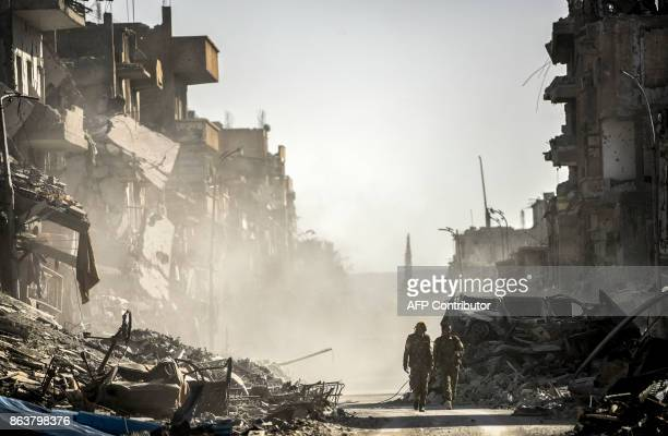 TOPSHOT Fighters of the Syrian Democratic Forces walk down a street in Raqa past destroyed vehicles and heavily damaged buildings on October 20 after...