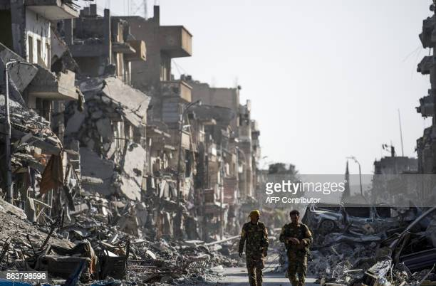 Fighters of the Syrian Democratic Forces walk down a street in Raqa past destroyed vehicles and heavily damaged buildings on October 20 after a...
