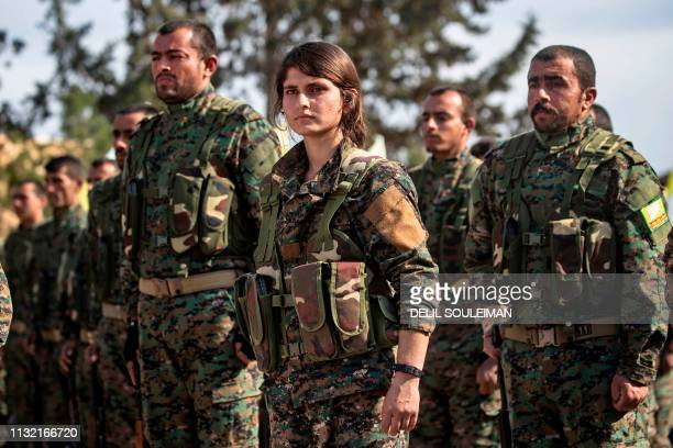 Fighters of the USbacked Kurdishled Syrian Democratic Forces take part in a parade to celebrate near the Omar oil field in the eastern Syrian Deir...