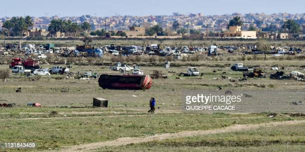 Fighters of the USbacked Kurdishled Syrian Democratic Forces walk through a field in the village of Baghouz in the eastern Syrian province of Deir...