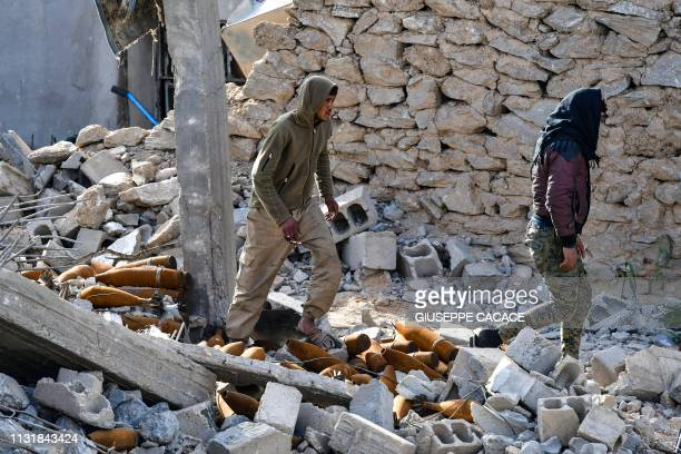Fighters of the USbacked Kurdishled Syrian Democratic Forces walk through debris and mortar shells in the village of Baghouz in the eastern Syrian...