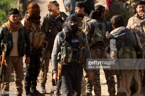 Fighters of the USbacked Syrian Democratic Forces take a rest in the frontline Syrian village of Baghouz on February 18 2018 SDF forces have been...