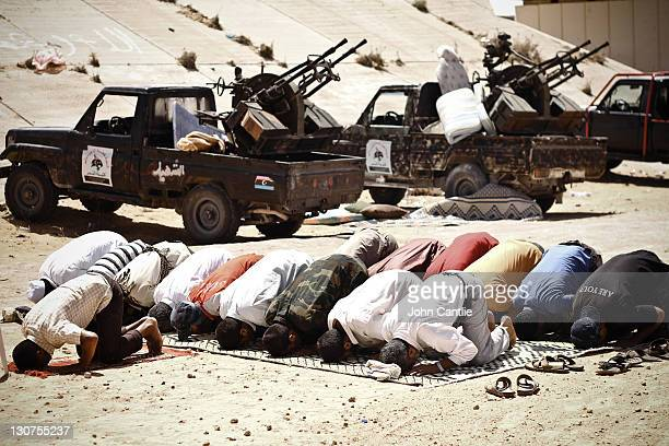 NTC fighters pray next to their gun trucks at an intersection on September 6 2011 in Misrata Libya Fighting in Libya has ceased following the killing...