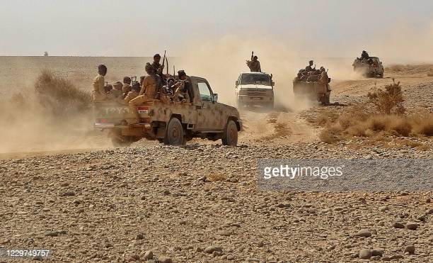 Fighters ride in pickup trucks as forces loyal to Yemen's Saudi-backed government clash with Huthi rebel fighters around the strategic...