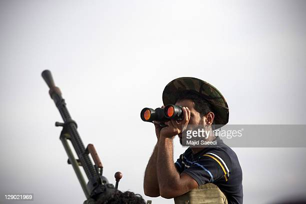 Fighters try to find their target to shoot on October 9, 2011 in Sirte, Libya. National Transitional Council fighters say this is the final assault...
