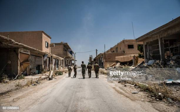 YPG fighters walk through the former ISIS and Jabat al Nusra stronghold of Tel Bark which was taken over by YPG fighters less than a year before...
