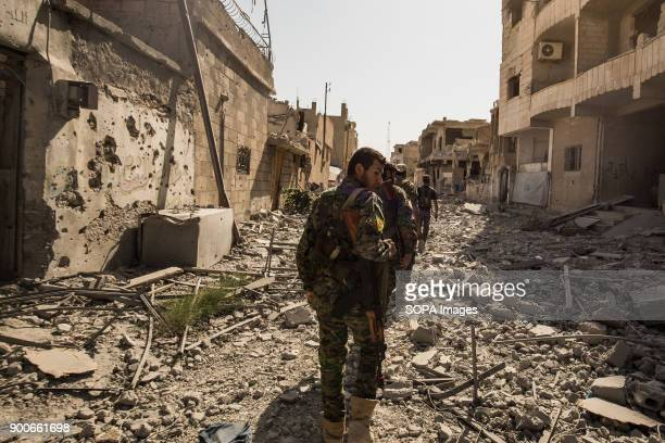 SDF fighters walking toward centrum of Raqqa city The overwhelming destruction of Raqqa speaks of a place that has been through more than just war...