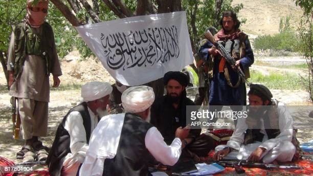 Fighters with Afghanistan's Taliban militia talk with villagers in Ahmad Aba district on the outskirts of Gardez the capital of Paktia province on...