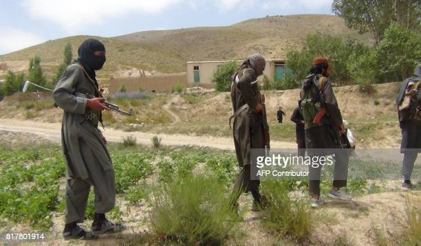 Fighters with Afghanistan's Taliban militia walk with their weapons in Ahmad Aba district on the outskirts of Gardez the capital of Paktia province...