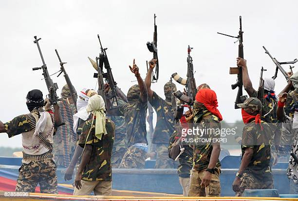 Fighters with the Movement for the Emancipation of the Niger Delta raise their riffles to celebrate news of a successful operation by their...