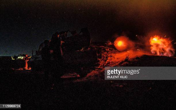 Fighters with the Syrian Democratic Forces fire a heavy machine gun in a position in the eastern Syrian province of Deir Ezzor outside the Islamic...