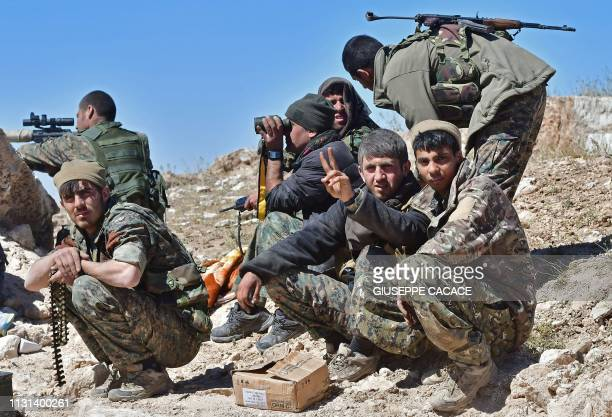Fighters with the Syrian Democratic Forces gather during a battle against the Islamic State group's last remaining position in the village of Baghouz...