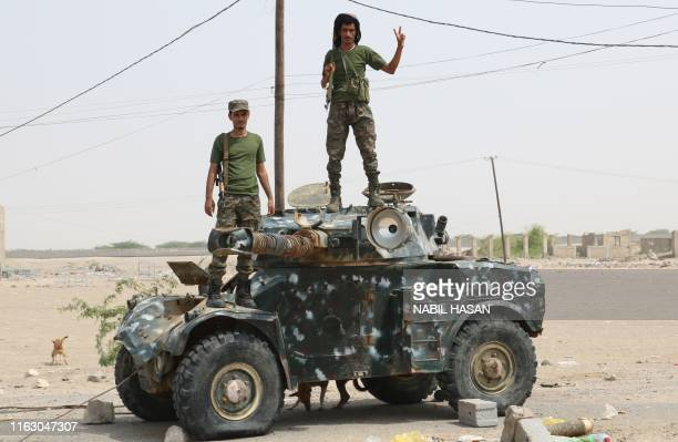Fighters with the UAE-trained Security Belt Forces loyal to the pro-independence Southern Transitional Council , stand atop a military vehicle near...